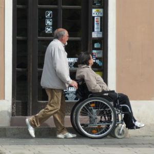An old man pushing a wheelchair